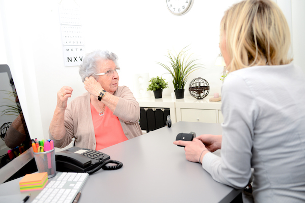 Audiologist demonstrates hearing aid techniques to client