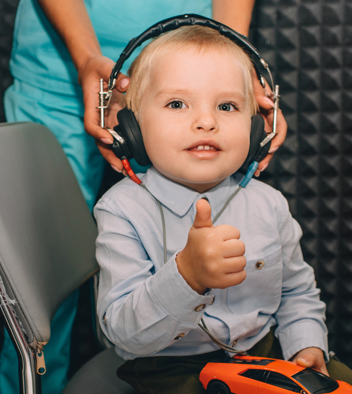 Pediatric client wearing headphones during a hearing exam