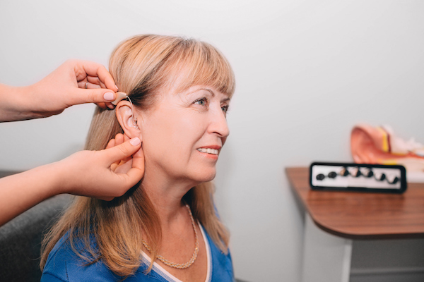 Audiologist adjusts client's hearing aid