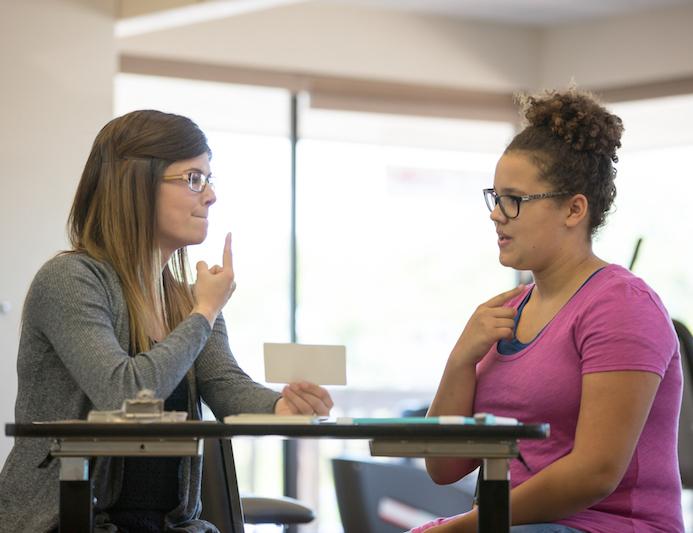 Speech language pathologist working a teenage client